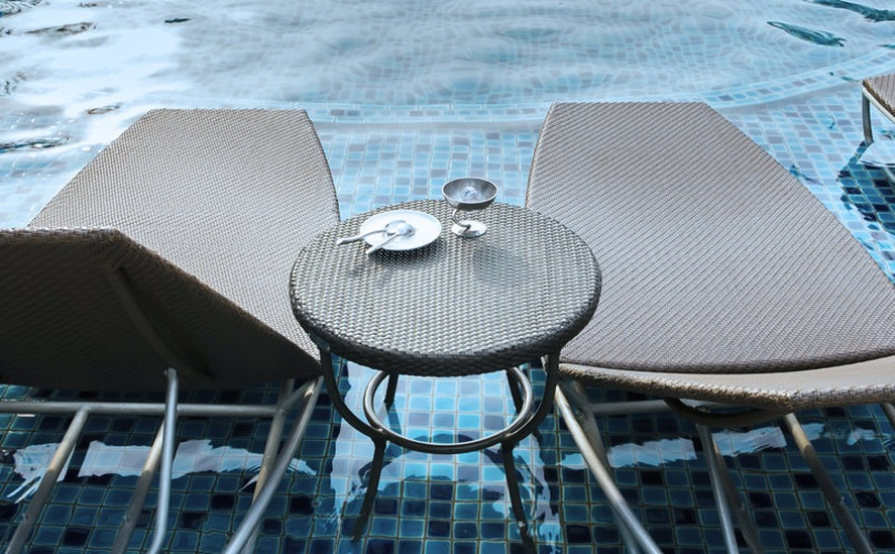 two lounge chairs with a small table between them in shallow pool ledge